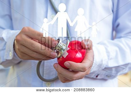 The doctor with a medical stethoscope check heart for family insurance and healthy care. Healthy and Family Concept