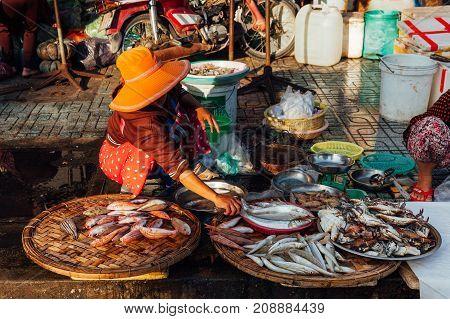 NHA TRANG VIETNAM - JULY 14: Vietnamese woman sells fish at the morning market in Nha Trang Vietnam on July 14 2016.