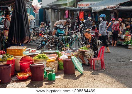 NHA TRANG VIETNAM - JULY 14: Vietnamese woman sells vegetables at the morning market in Nha Trang Vietnam on July 14 2016.
