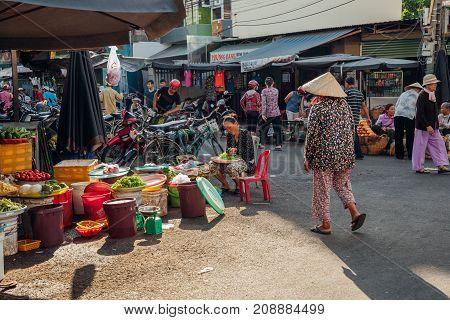 NHA TRANG VIETNAM - JULY 14: Vietnamese woman in conical hat walks at the morning market in Nha Trang Vietnam on July 14 2016.