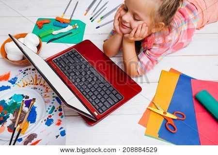 Creative inspiration. Funny leisure time. Little girl watching cartoons, looking for artistic ideas. Laptop with white screen mockup, creativity concept