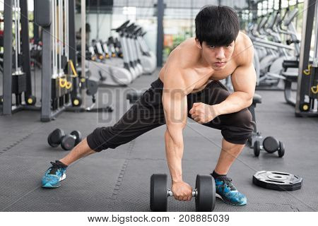 Man Lift Dumbbell In Gym. Bodybuilder Male Working Out In Fitness Center. Sport Guy Doing Exercises
