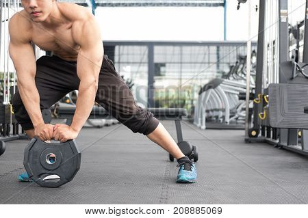 Young Man Bodybuilder Execute Exercise In Fitness Center. Male Athlete Lift Heavy Weight Barbell Pla