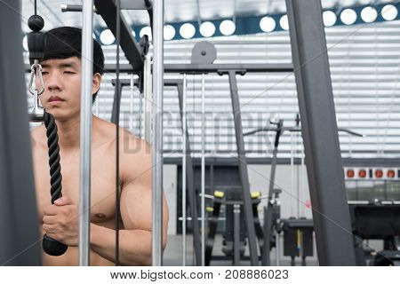 Young Man Execute Exercise With Weightlifting Machine In Fitness Center. Male Athlete Pump Up Muscle