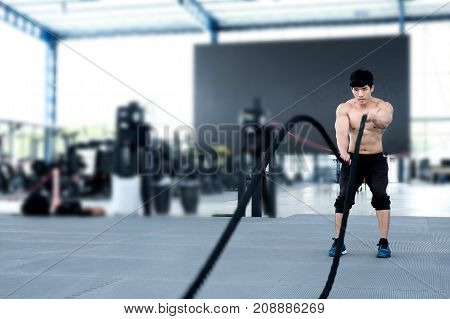Young Man Execute Exercise In Fitness Center. Male Athlete Training With Battle Rope In Gym. Sporty