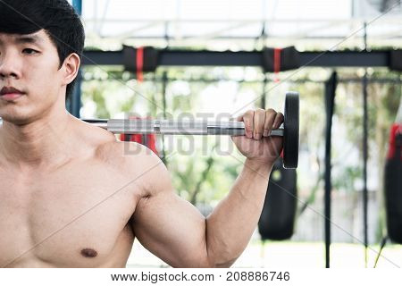 Muscular Man Execute Exercise In Fitness Center. Male Athlete Pump Up Muscle In Gym. Weightlifter Wo
