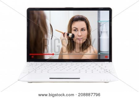 beauty blog - young woman showing how to apply make up in video on laptop screen