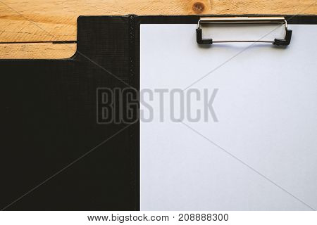 Black clipboard with white paper on wooden table