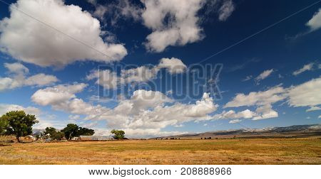 Panoramic American Rural Farmland Countryside Landscape With Blue Cloudyscape and mountains in the distance