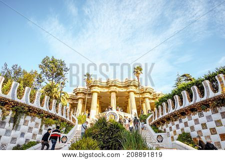 BARCELONA, SPAIN - August 17, 2017: View on the Dragon stairway and terrace with tourists in Guell park, famous public park with gardens and architectonic elements designed by Antoni Gaudi