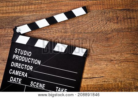 Opened clapper board or slate film on wooden background.