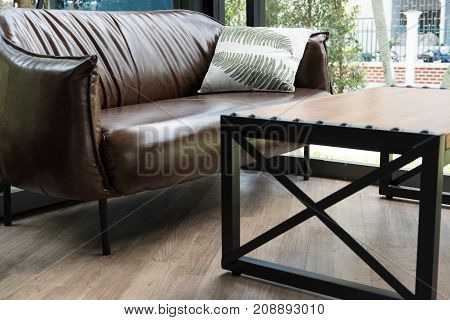 Table, Chair, Brown Leather Sofa Near Window At Restaurant Or Cafe