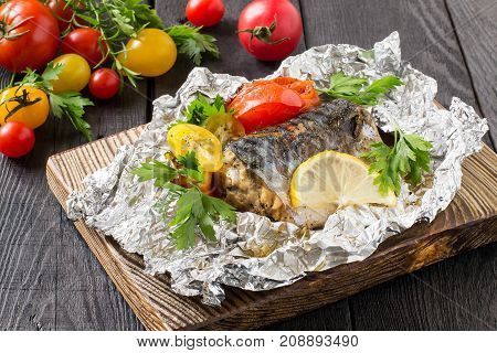 Mackerel baked with tomatoes in foil. Mackerel in foil lies on wooden plate on dark wooden table. Also lie fresh tomatoes and herbs. Healthy and dietary food