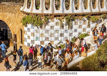 BARCELONA, SPAIN - August 17, 2017: Close-up view on the Dragon stairway with tourists in Guell park, famous public park with gardens and architectonic elements designed by Antoni Gaudi