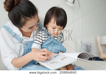Vietnamese Mother And Little Daughter Girl Reading A Book In The Morning Together In The Living Room