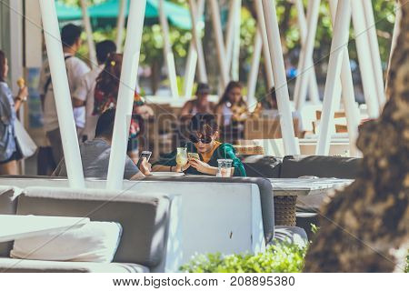 BALI, INDONESIA - OCTOBER 12, 2017: Couple of happy tourists in outdoors cafe