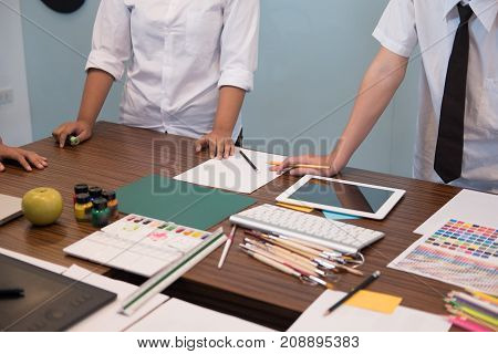 interior designer working with graphic tablet at workplace. artist discussing design and idea at office. business people brainstorming for new creativity project. teamwork partnership concept