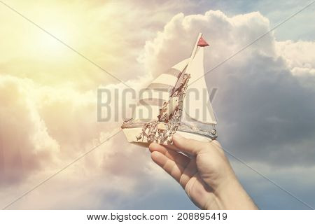 Handmade ship in a man's hand against a background of clouds as a symbol of travel and dreams.Toning