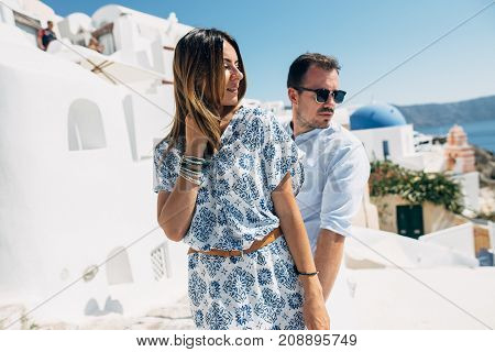 Happy Couple Hugging And Laughing Together With A View Of Santorini