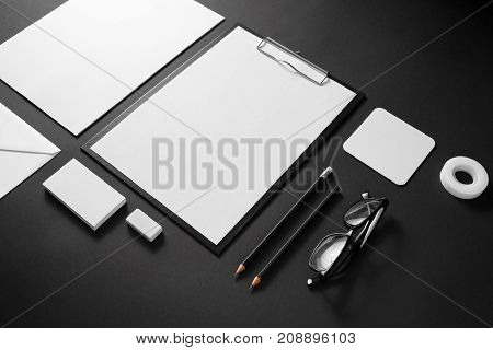 Photo of blank stationery set on black paper background. Corporate identity template. Responsive design mockup.