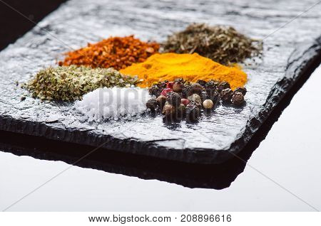 Different spices and herbs on a black slate. Indian spices. Ingredients for cooking. Healthy eating concept. Various spices on dark background.
