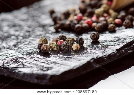Different pepper spices on a black slate. Ingredients for cooking. Healthy eating concept. Various spices on dark background. Healthy food.
