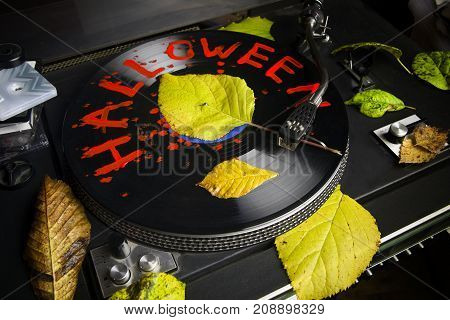 A vinyl player autumn leaves and vinyl record with Halloween writing. Closeup studio photo