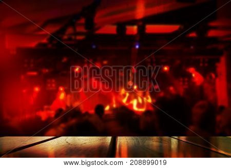 top of wood table with blur red light music performance party in bar pub or club at night background