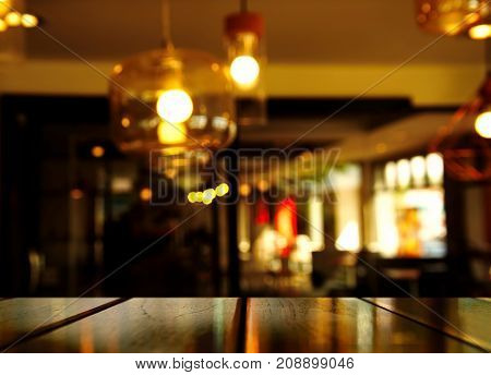 top of black wood table with blur lam in bar or bub in the dark night city background