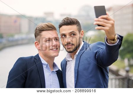 two handsome businessmen talking a selfie and having fun