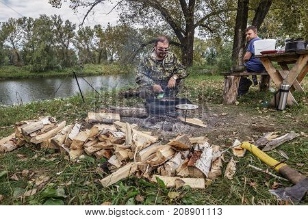 Two men cook food at the campfire