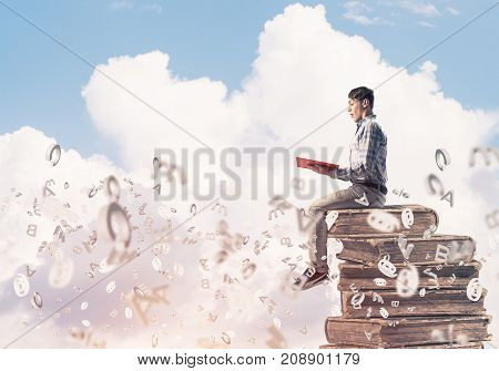 Young shocked man in casual sitting on pile of books with one in hands