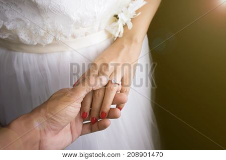 Wedding love couple concept : groom put wedding rings on bride finger on wedding day event sunrise effect with lens flare