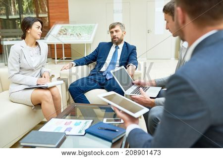 Multi-ethnic group of managers in formalwear brainstorming on promising start-up project while having working meeting at spacious boardroom