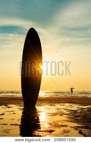 Silhouette of surf man surfing with a surfboard on the seashore beach at sunset time. Handsome Asia man model in his 20s.