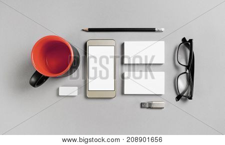 Office supplies and gadgets on gray paper background. Blank corporate stationery set. Branding mockup. Top view.