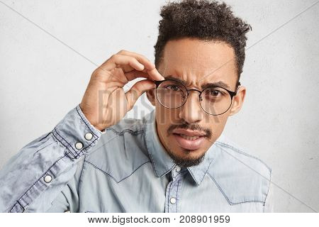 Portrait Of Handsome Bearded Male Student Nerd Wears Round Spectacles, Looks Attentively At Camera,