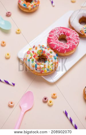 Preparation for the holiday. Colorful american donuts on pink background