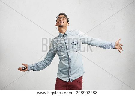 Pleased Excited Male Wears Trendy Clothes, Listens Joyful Songs On Smart Phone With Earphones, Dance