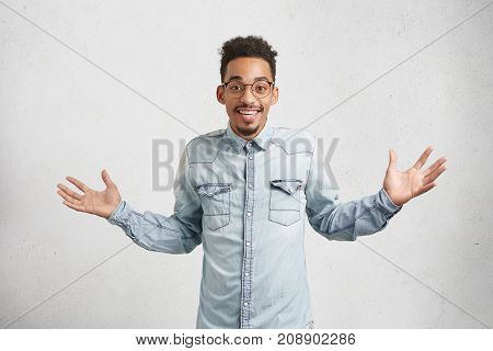 Portrait Of Joyful Happy Male With Trendy Hairdo, Gestures As Being Pleased To Hear Positive News. S