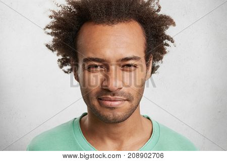 Close Up Portrait Of Suspicious Dark Skinned Man Wears Green Sweater, Has Serious Expression, Thinks