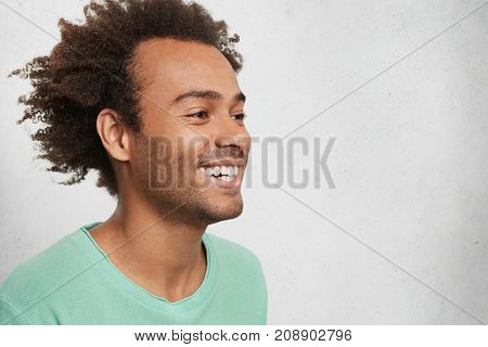 Sideways Portrait Of Glad Young Smiling Dark Skinned Male With Crisp Bushy Hair, Looks Aside, Being