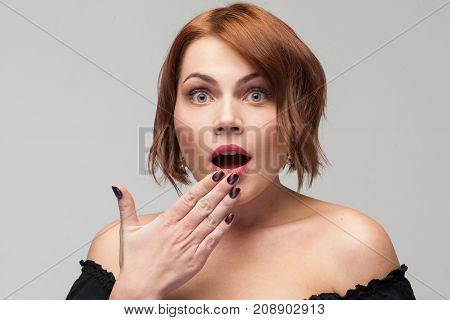 Shocking gossip. Ashamed young lady. Astonished pretty female, surprising news, daze and big size concept. Beautiful amazed woman on grey background,