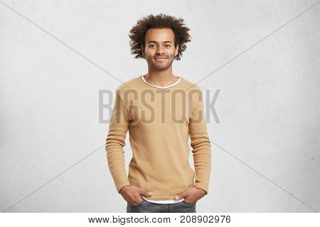 Delightful Dark Skinned Man In Sweater And Jeans, Look Pleased At Camera, Has Good Mood As Comes Hom