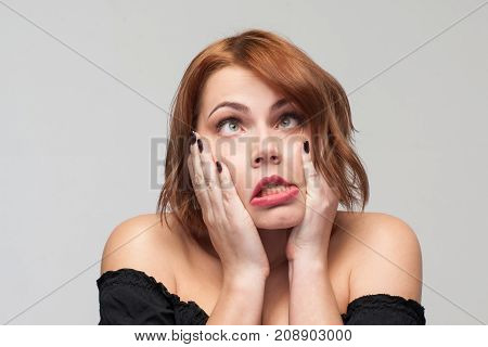 Forever young. Tired playful woman. Funny girl portrait on grey background with free space. Problems in life