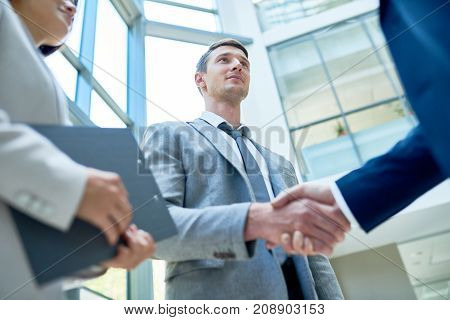 Low angle view of handsome young entrepreneur wearing classical suit shaking hand of business partner while standing at spacious office lobby