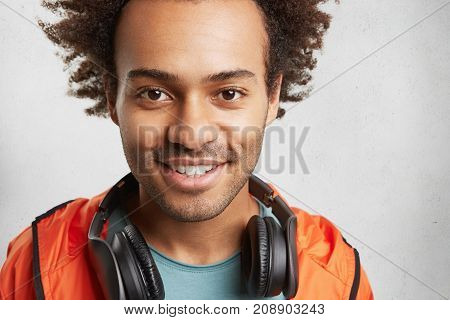 Close Up Portrait Of Unshaven Handsome Young Hipster Guy Looks With Dark Shining Eyes And Pleased Sm