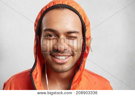 Sweaty Male Couch Or Trainer, Wears Hood, Listens Music With Earphones And Electronic Device, Blink