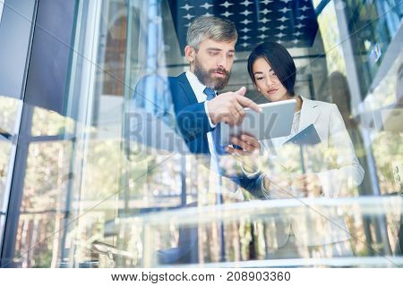 Confident bearded businessman holding digital tablet in hands while showing work results to his pretty young colleague, they standing at panoramic window of office lobby