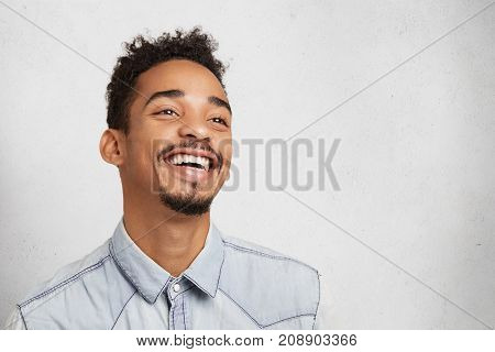 Glad Positive Young Mixed Race Man With Mustache And Beard, Smiles Happily As Being Promoted At Work
